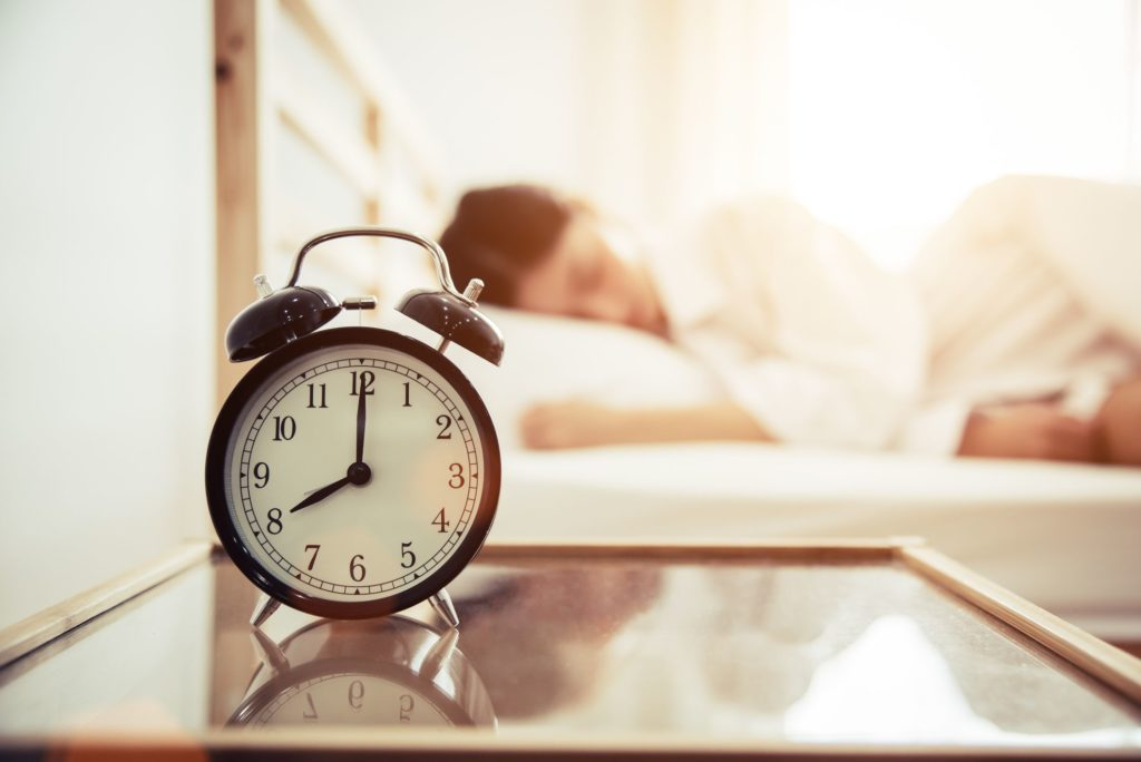 close up of alarm clock on table by woman sleeping royalty free image 932506546 1551805426
